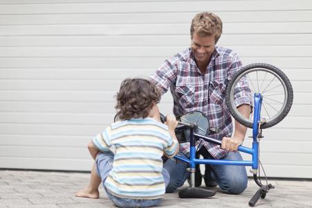 agachado: Padre ayudando a hijo a arreglar la bicicleta