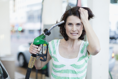 fillup: Frustrated woman pumping gas into hair