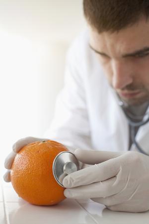 specimen testing: Scientist using stethoscope on orange LANG_EVOIMAGES