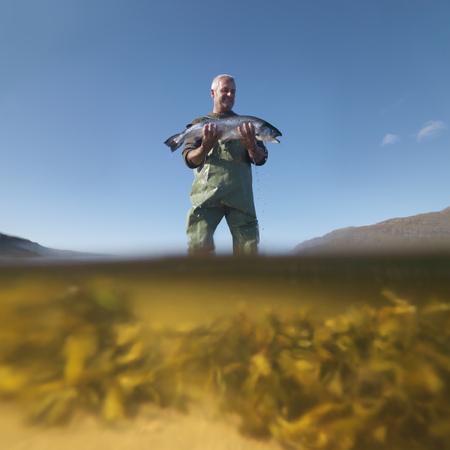 wade: Fisherman with salmon in still lake