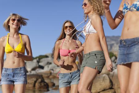 Women in bikinis walking on beach