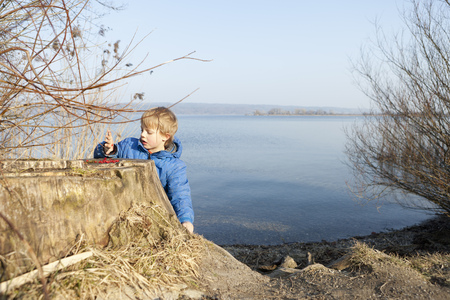 Boy playing with berries by lake