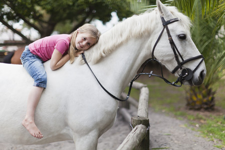 uncomplicated: Smiling girl riding horse in yard