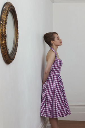 Woman leaning on wall in hallway LANG_EVOIMAGES