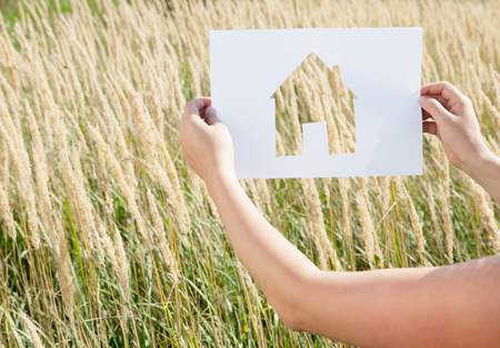 Woman holding paper house cut out LANG_EVOIMAGES