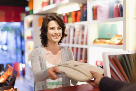 spender: Woman buying purse in store LANG_EVOIMAGES
