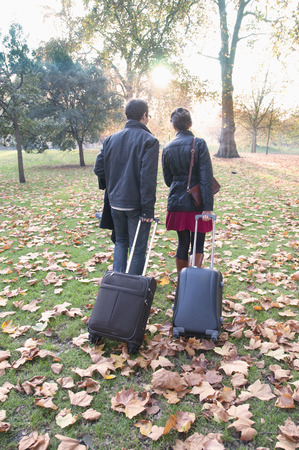 leafed: Couple rolling luggage in park