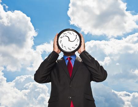Businessman holding warped clock LANG_EVOIMAGES
