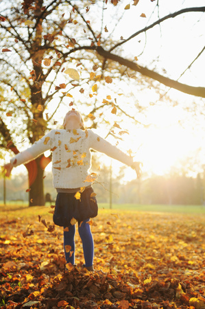 adolescencia: Smiling girl playing in autumn leaves LANG_EVOIMAGES