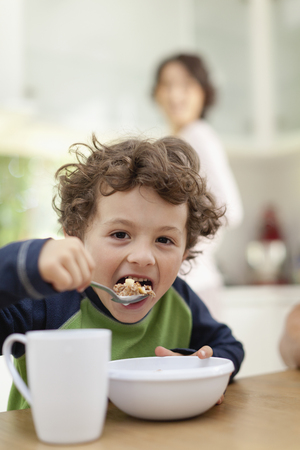 Boy eating breakfast in kitchen