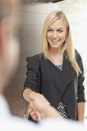 Smiling business people shaking hands LANG_EVOIMAGES