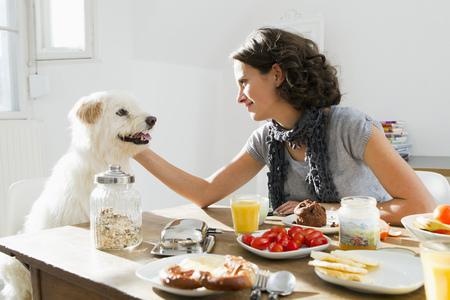 Woman petting dog at table