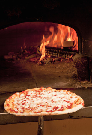 blazed: Chef pulling pizza from oven