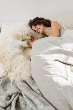 snuggle: Woman relaxing in bed with dog LANG_EVOIMAGES