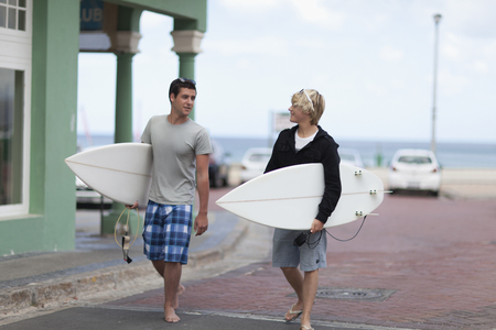 Teenage boys carrying surfboards LANG_EVOIMAGES