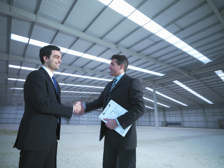 agrees: Businessmen shaking hands in warehouse