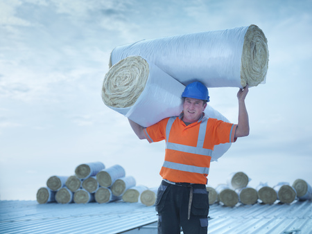arms lifted up: Worker carrying insulation on roof