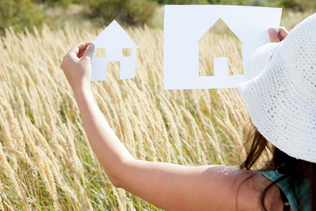 dwelling: Woman holding paper house cut outs LANG_EVOIMAGES