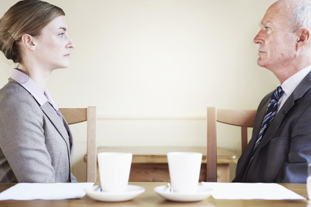 confrontational: Serious business people sitting in cafe