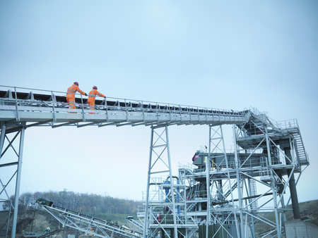 Worker climbing screening conveyor LANG_EVOIMAGES