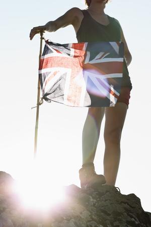 cease: Hiker planting Union Jack flag LANG_EVOIMAGES