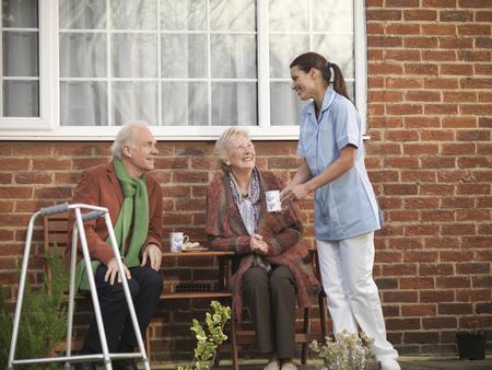 bringing: Nurse bringing older couple coffee