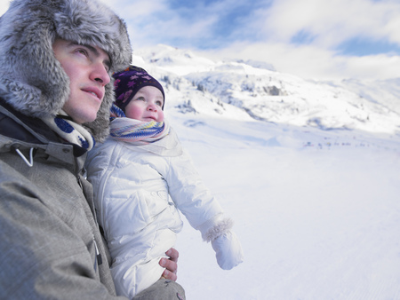 mountainous: Father holding baby in snowy landscape