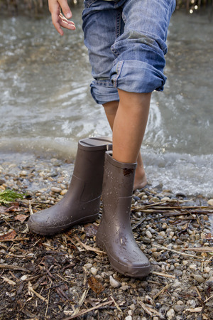 treading: Girl taking off rain boots by pond