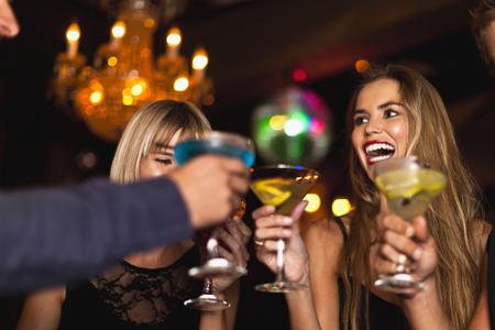 appendages: Smiling women having cocktails in club LANG_EVOIMAGES