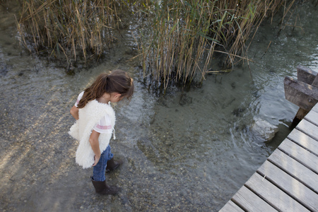 swampland: Girl in boots walking in pond LANG_EVOIMAGES