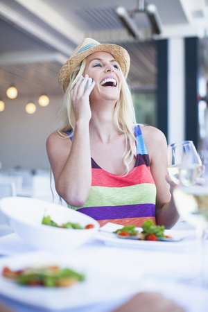 Woman talking on cell phone in cafe