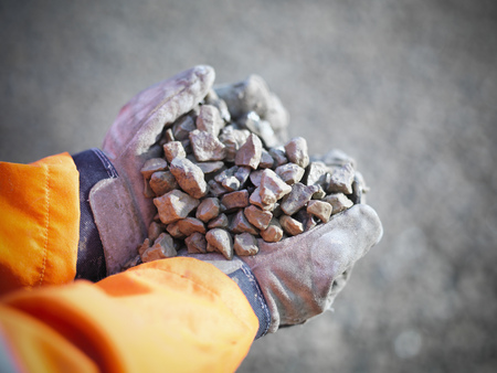 defended: Worker with handful of quarry rocks