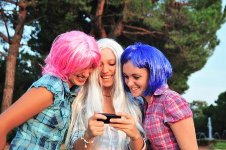 Teenage girls wearing colorful wigs LANG_EVOIMAGES