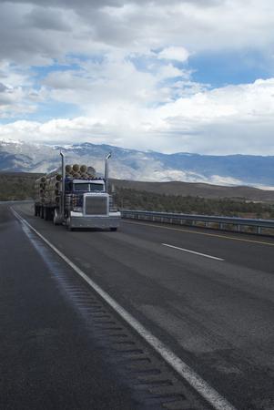 journeying: Truck carrying logs in rural landscape LANG_EVOIMAGES