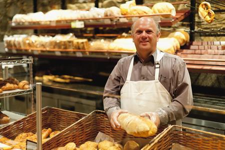 Smiling baker holding loaf of bread