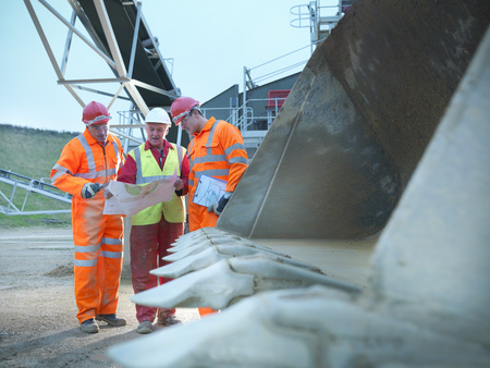 personas reunidas: Construction workers reading blueprints