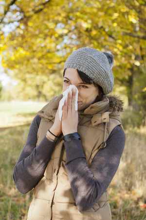 sickly: Woman blowing her nose in park