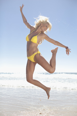 Woman jumping for joy on beach