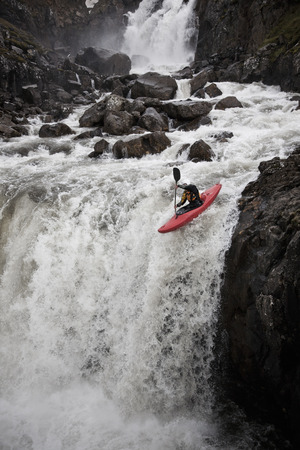 Man canoeing over rocky waterfall LANG_EVOIMAGES