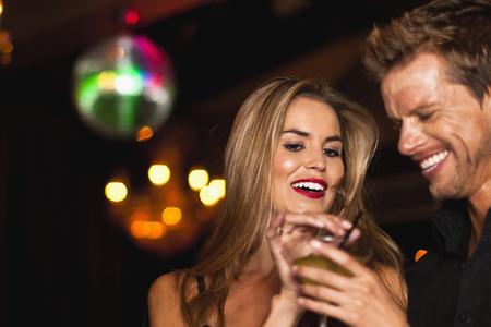 Sonriente pareja de tener cócteles en el club