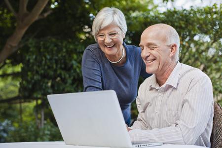 typist: Older couple using laptop outdoors
