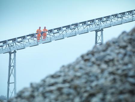 ascends: Worker climbing screening conveyor LANG_EVOIMAGES