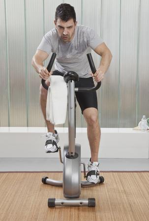 Struggling man using exercise machine