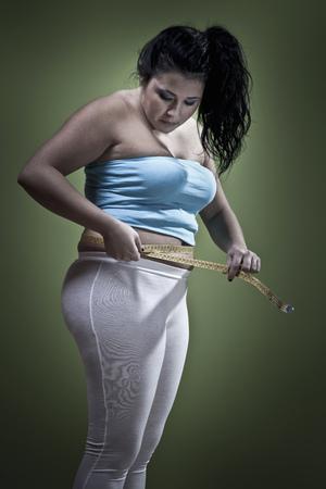 Woman measuring her waistline LANG_EVOIMAGES