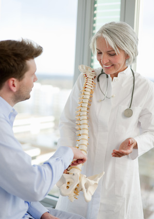 orthopedist: Doctor showing spine model to patient LANG_EVOIMAGES