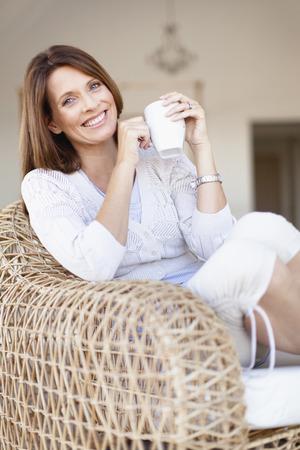 mornings: Older woman having coffee in armchair