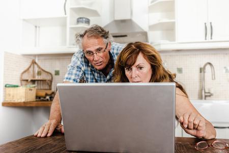 Older couple using laptop in kitchen LANG_EVOIMAGES