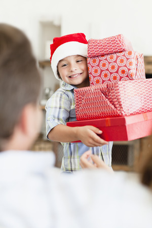 Boy in Santa hat with Christmas gifts LANG_EVOIMAGES
