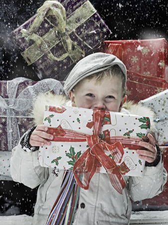 Boy holding Christmas present in snow