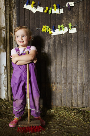 Girl in overalls sweeping in barn LANG_EVOIMAGES